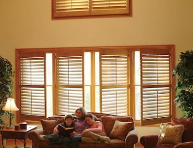 "Sussex Shutters, inside mount over existing oak olding, 3-1/2"" louvers, divider rail, quarter sunburst with continuous frame, oak mantel stain."
